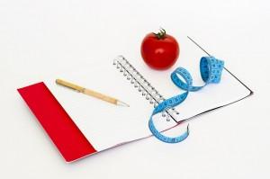 grafika, na stole sa nachádza jablko, meter a zápisník